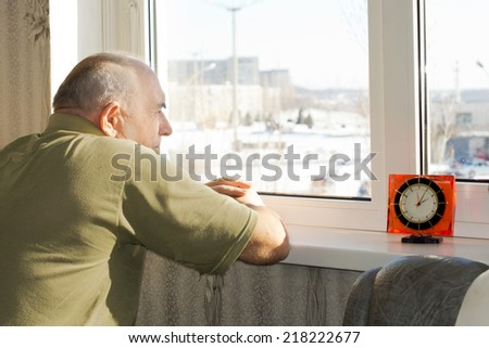 Bored senior man waiting patiently for time to pass as he stands staring disconsolately out of a window on a sunny day waiting for someone to arrive for a visit