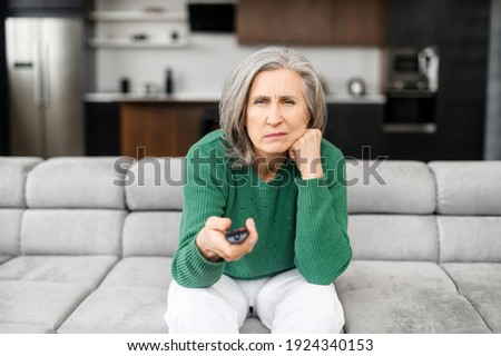 Bored senior woman spends leisure time watching TV shows, movies. The mature elderly female sitting on the couch alone with a remote controller and switching channels, feels drearily. Front view Photo stock ©