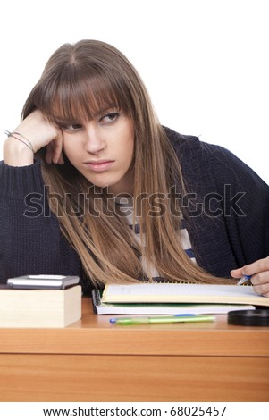 Bored student doing her homework on a desk