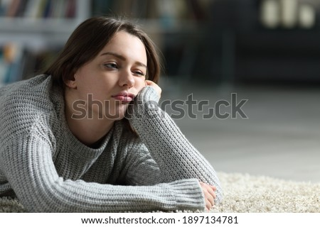 Bored teen looking away lying on the floor at home Photo stock ©