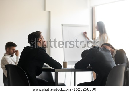 Bored unmotivated diverse team of employees feeling lack of interest during educational workshop. Sleepy manager feeling tired at lecture. Yawning businessman distracted from corporate training.
