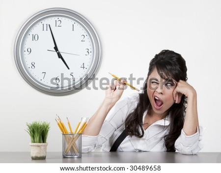 Bored woman at her desk at the end of day aiming a pencil