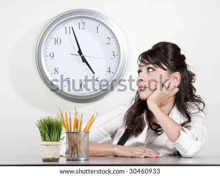 Bored woman at her desk at the end of the day