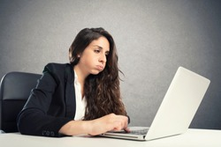 Bored woman snorts in the office while working on the laptop