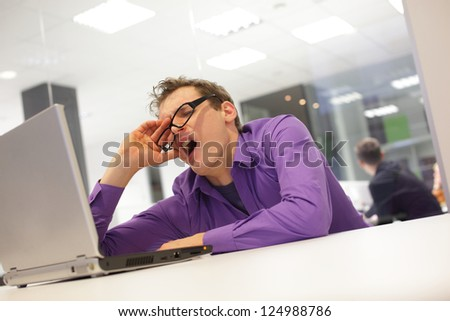 bored yawning businessman working with laptop supporting his head on his hand in office space