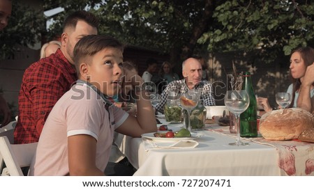 Bored young boy feeling annoyed sitting at table on family reunion party. Сток-фото ©