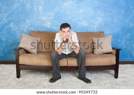 Bored young Caucasian man rests on sofa with hands on face - stock photo