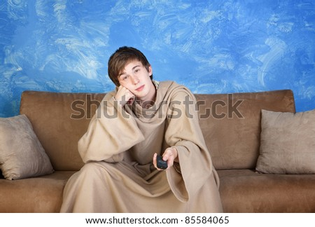 Bored young man in bathrobe and remote control