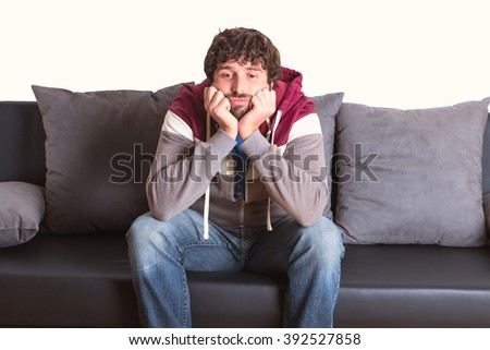 bored young man sitting at home on sofa