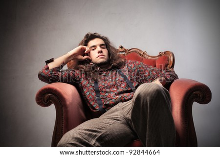 Bored young man sitting on an armchair