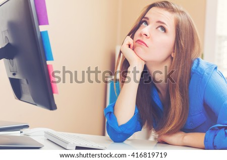Bored young woman sitting at her desk in front of the computer