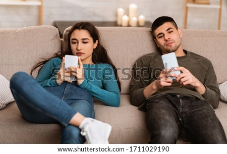 Boredom Concept. Young couple using smart phones, sitting on couch at home during self isolation Photo stock ©