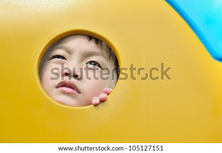 Boring face expression of asian boy in playground hole.