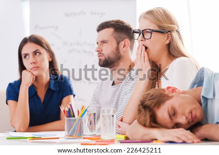 Boring presentation. Group of young business people in smart casual wear looking bored while sitting together at the table and looking away