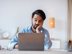 Boring Work. Young arab freelancer guy working on laptop, looking at screen with bored face expression, eastern man tired of monotonous work, sitting at desk with computer and resting head on hand