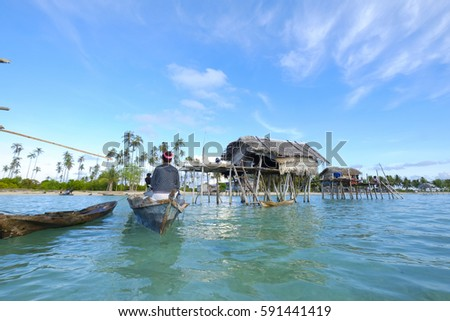 Borneo Island, Sabah  Malaysia - 02 Mach 2017  : Wonderful view of borneo island and with daily routine panorama of sea gypsy family at their house built in beautiful sea and blue sky background  #591441419