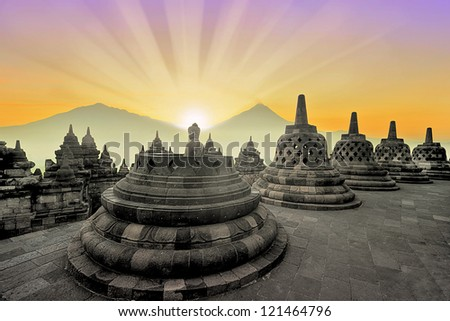 Borobudur temple at sunrise with mountain overview - stock photo