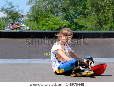 Borred girl with roller skates sitting lonely in the park in a sunny sumer day Stock fotó ©