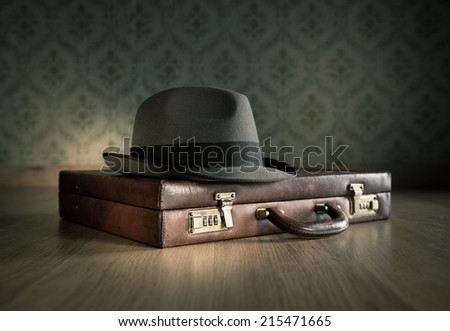 Borsalino hat on leather vintage briefcase on wooden surface with vintage wallpaper on background. Stock photo ©