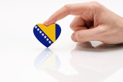Bosnia and Herzegovrina flag. Love and respect Bosnia and Herzegovina. A man's hand holds a heart in the shape of the flag on a white glass surface. The concept of Bosnian patriotism and pride.