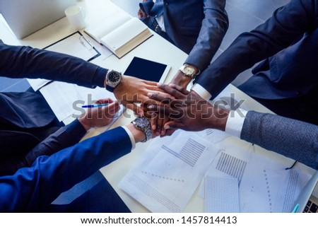 boss afro businessmen talking with arab and india partners colleague, multiethnic team sitting at a table with a laptop and documents in the office with panorama window.contract signature idea