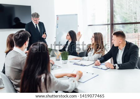 Boss  businessman holding papers hands and smiling.Young team of coworkers making great business discussion in modern coworking office.