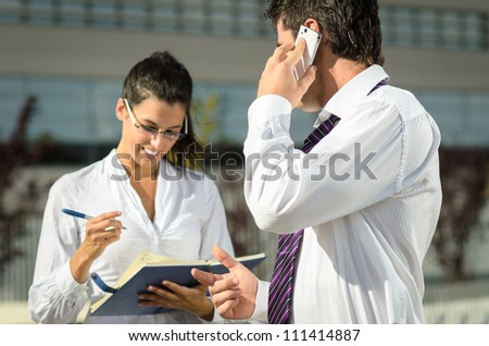 Boss dictating notes to his cheerful assistant while talking by phone.