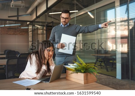 Boss dismissing an employee. Dejected fired office worker carrying a box full of belongings. Getting fired. Angry boss pointing female employee on exit way. Boss firing a young employee in the office