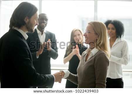 Boss handshaking employee congratulating with promotion while diverse colleagues clapping applauding, company ceo awarding appreciating motivating office worker for good work result by shaking hands