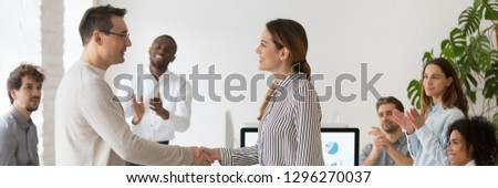 Boss handshaking with promoted female worker congratulating with success showing appreciation with good work result diverse colleagues clapping hands. Horizontal photo banner for website header design #1296270037
