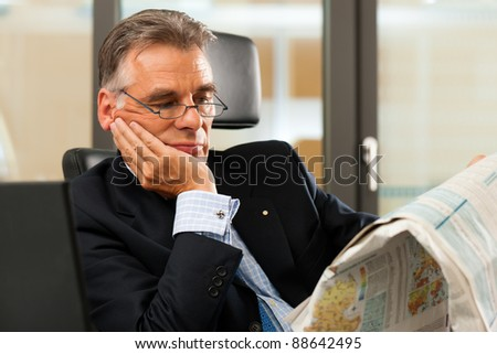 Boss in his office reading newspaper - the business section