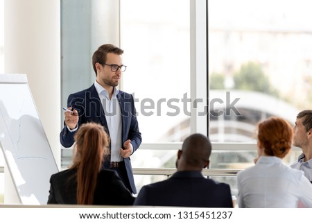 Boss in suit presenting new project business plan to audience multiracial employees or clients customers investors, male coach company trainer share knowledge use flipchart, teamwork education concept