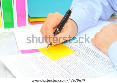 Boss is making correction notes in a contract