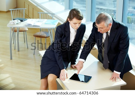 Boss pointing at tablet screen during explanation of something to secretary