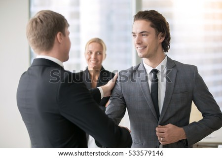 Boss promoting male subordinate. Two businessmen handshaking, congratulating on promotion, hired young consultant, promising innovation, ready for new heights, getting higher pay rate, financial bonus