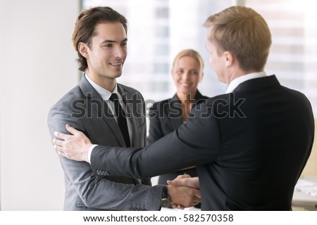 Boss promoting young subordinate. Two businessmen handshaking, congratulating on promotion, ensure long-term prosperity, human resource solutions, hired effective team, advancement of company position