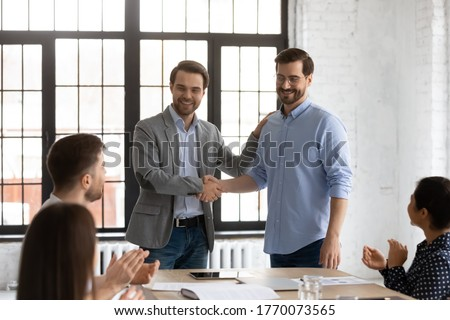 Boss shake hands introduces new employee to members during briefing in board room, staff clap hands encourage newcomer welcoming express regard. Praise and appreciation, best worker of month concept Photo stock ©