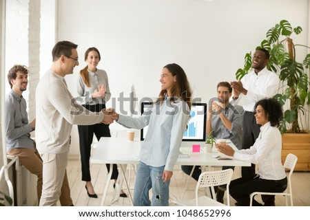 Boss shaking hand of young shy woman congratulating successful employee with promotion, hiring intern, appreciating for good work result, rewarding while business team applauding supporting colleague
