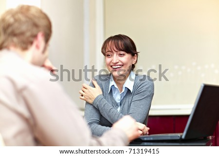 Boss talking to his employee and she is smiling