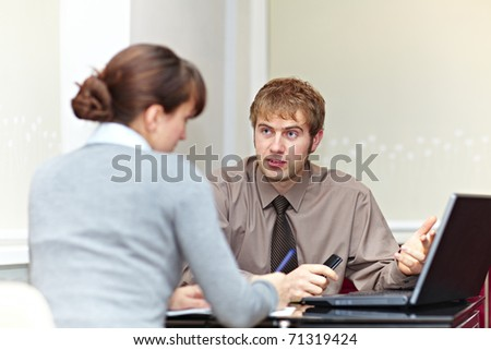 Boss talking to his secretary and showing her something on laptop computer