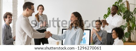 Boss welcoming new employee hired intern female, mixed race woman feel happy promoted receive appreciation for good work result from company head colleagues applauding banner for website header design