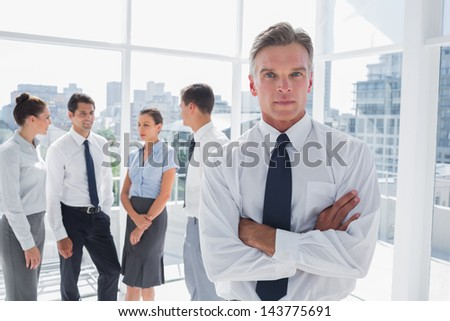 Boss with arms folded standing in a modern office with colleagues behind