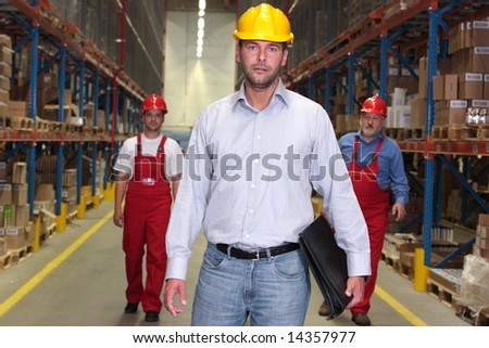 boss with briefcase at the front of team of workforce in warehouse - 2 or 3 workers in background