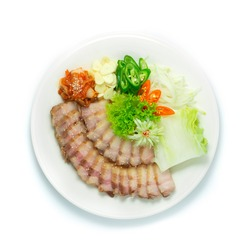 Bossam Korean Boiled Pork wraps Served Kimchi,Green Chili, Garlic, onion and Chinese Cabbage eat with Chili Spicy Sauce Korean Food Style decorate with carved Leek and vegetable topview