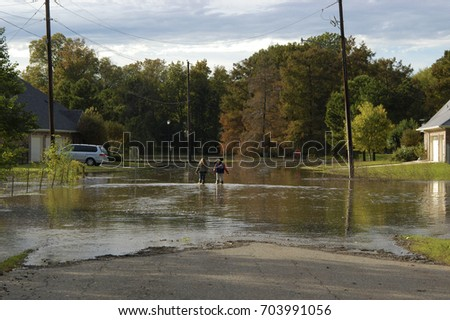 BOSSIER CITY, LA. - OCT. 30, 2009: School children wade through a flooded residential street.                                 #703991056