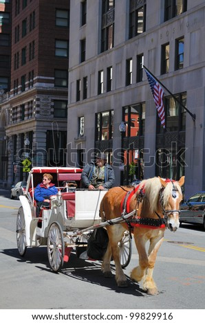 BOSTON - APRIL 9: A horse-drawn carriage ride April 9, 2012 in Boston, MA. The nostalgic transport method is often used by tourists in various global cities as a vehicle for sightseeing. - stock photo