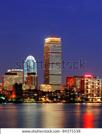 Boston city skyline at dusk with Prudential Tower and urban skyscrapers over Charles River with lights and reflections.