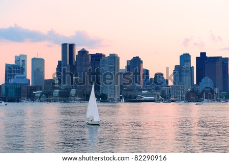 Boston downtown sunset skyline over river with skyscrapers and boat.