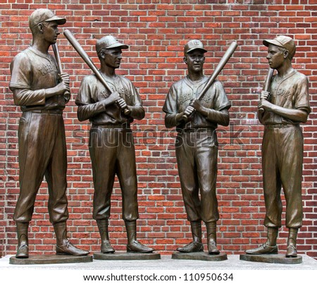 BOSTON, MA - AUGUST 10: The landmark statues of Ted Williams, Bobby Doerr, Johnny Pesky, and Dom Dimaggio attract hundreds of baseball fans to the Fenway Park in Boston, MA for souvenir photos on August 10, 2012.
