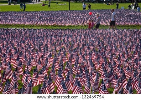 BOSTON - MAY 27: People among 20,000 American Flags are displayed for every resident of Massachusetts who died in a war over the past 100 years, Boston Common on May 27, 2012 in Boston, MA.